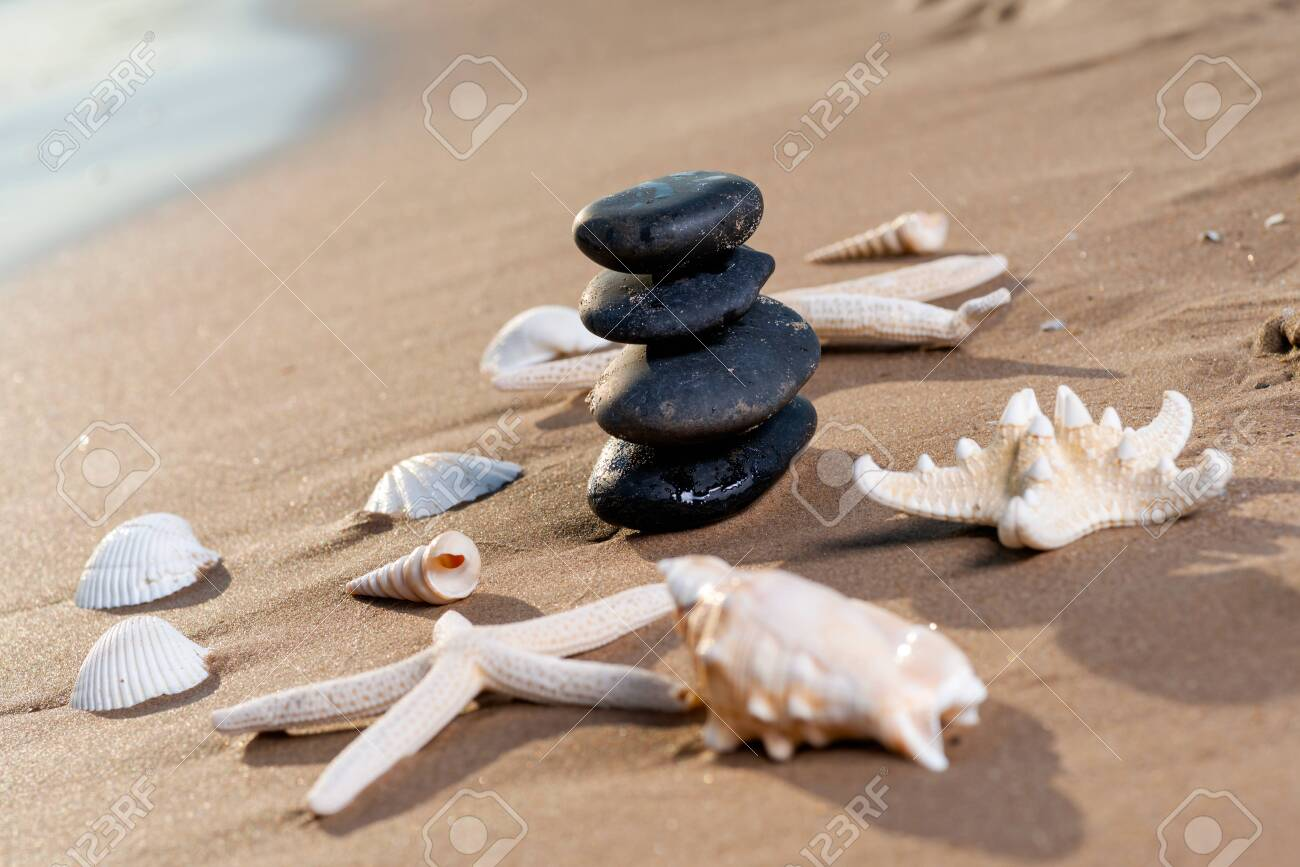 Spa composition - stacked Basalt Stones, Seashells and Sea Stars on the beach at sunrise in front of the ocean. Wellness, Balance and Relax concept. - 128873560