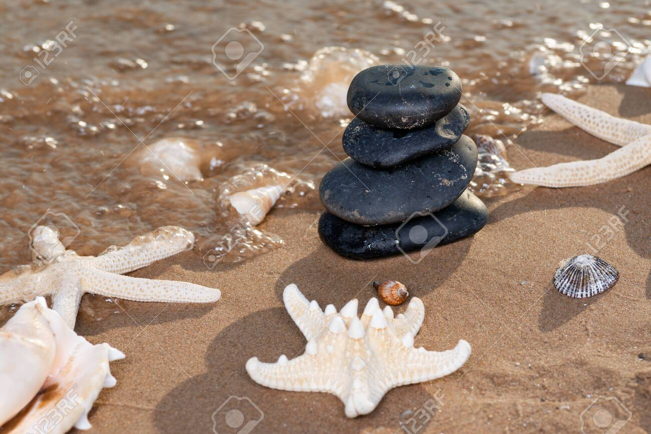 Spa composition - stacked Basalt Stones, Seashells and Sea Stars on the beach at sunrise in front of the ocean. Wellness, Balance and Relax concept. - 128873559