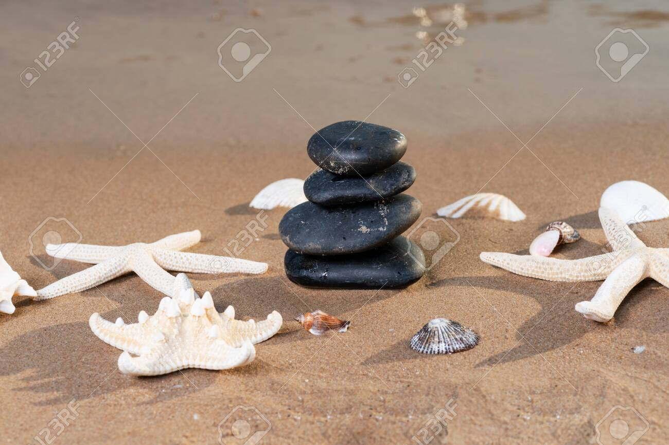 Spa composition - stacked Basalt Stones, Seashells and Sea Stars on the beach at sunrise in front of the ocean. Wellness, Balance and Relax concept. - 128873561