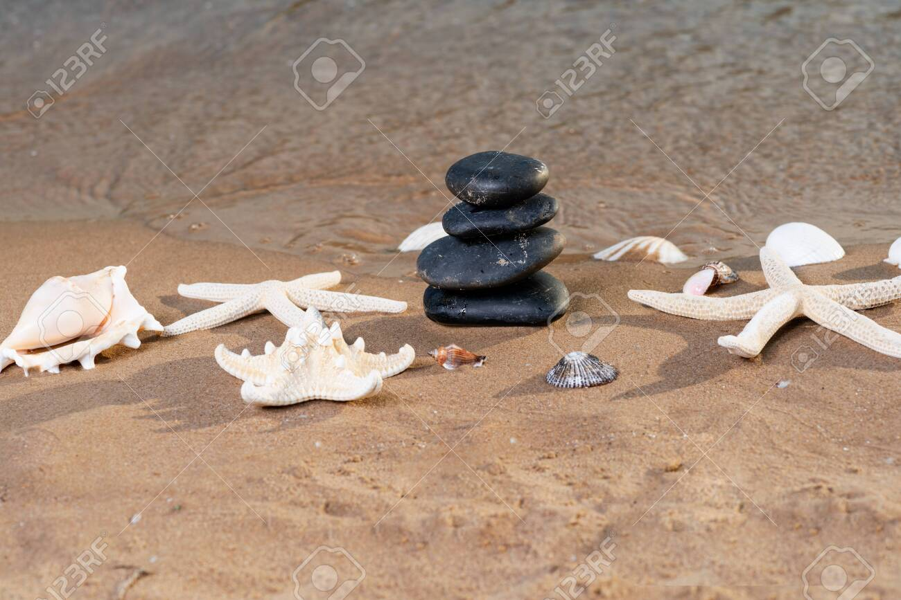 Spa composition - stacked Basalt Stones, Seashells and Sea Stars on the beach at sunrise in front of the ocean. Wellness, Balance and Relax concept. - 128873564
