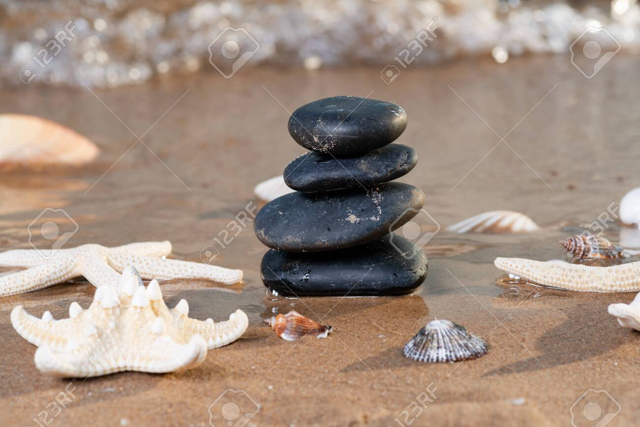 Spa composition - stacked Basalt Stones, Seashells and Sea Stars on the beach at sunrise in front of the ocean. Wellness, Balance and Relax concept. - 128873565