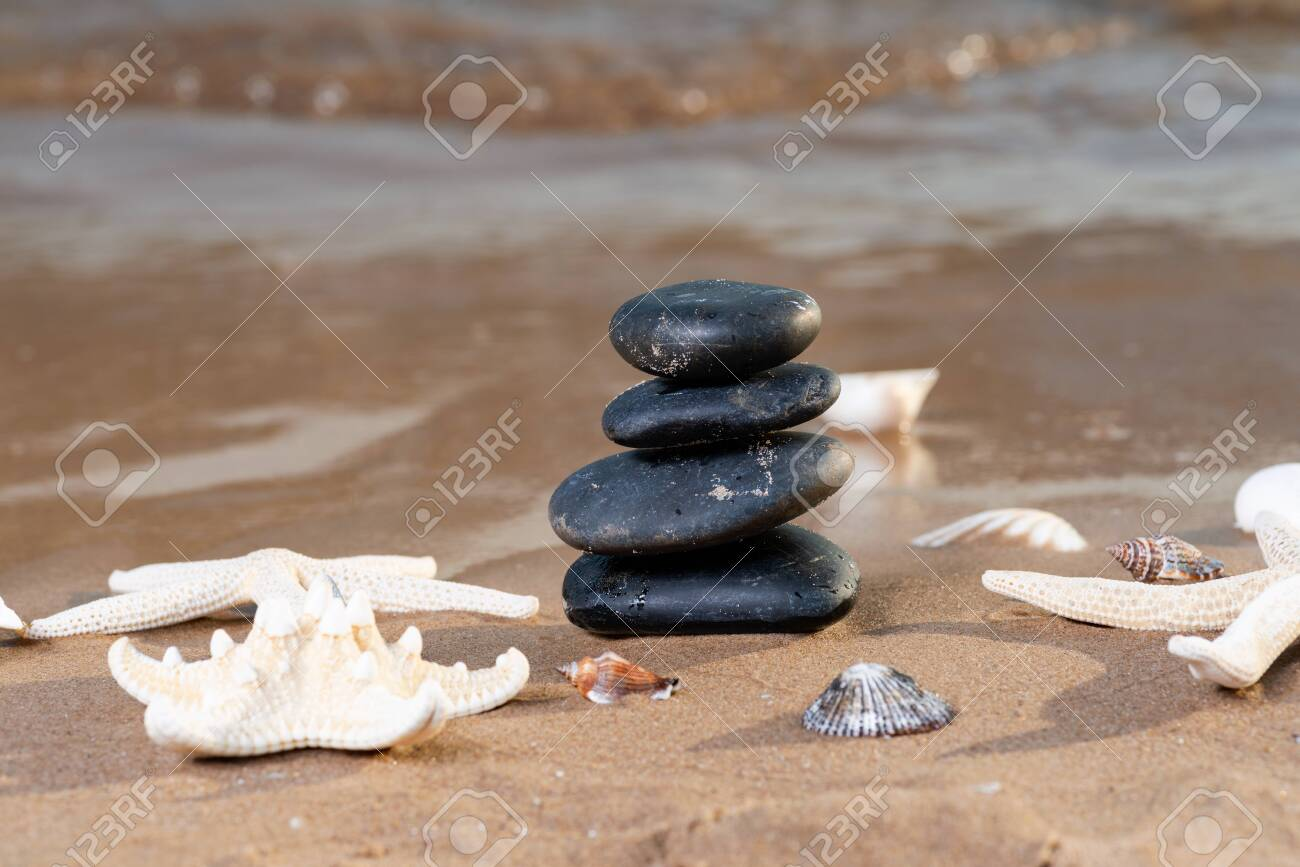 Spa composition - stacked Basalt Stones, Seashells and Sea Stars on the beach at sunrise in front of the ocean. Wellness, Balance and Relax concept. - 128873567