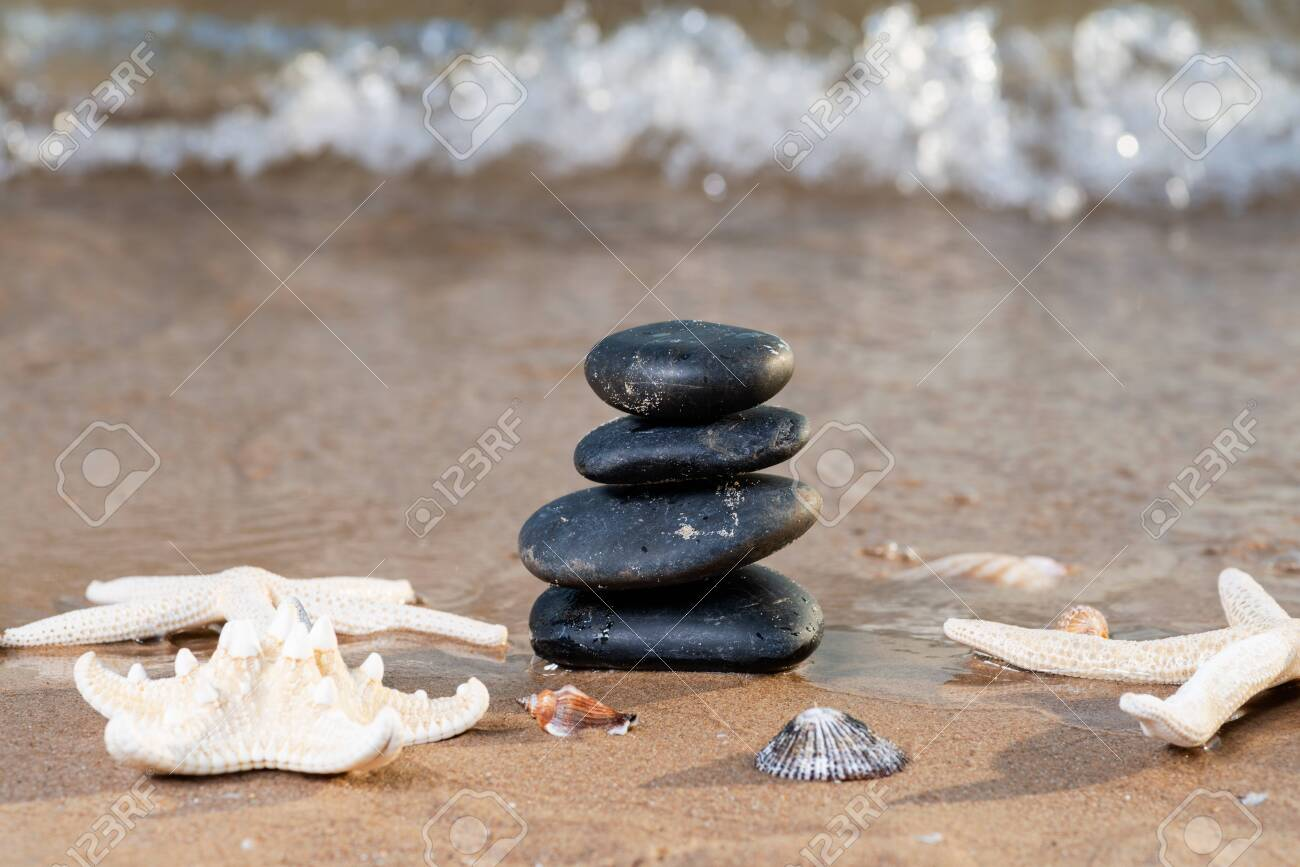 Spa composition - stacked Basalt Stones, Seashells and Sea Stars on the beach at sunrise in front of the ocean. Wellness, Balance and Relax concept. - 128873569