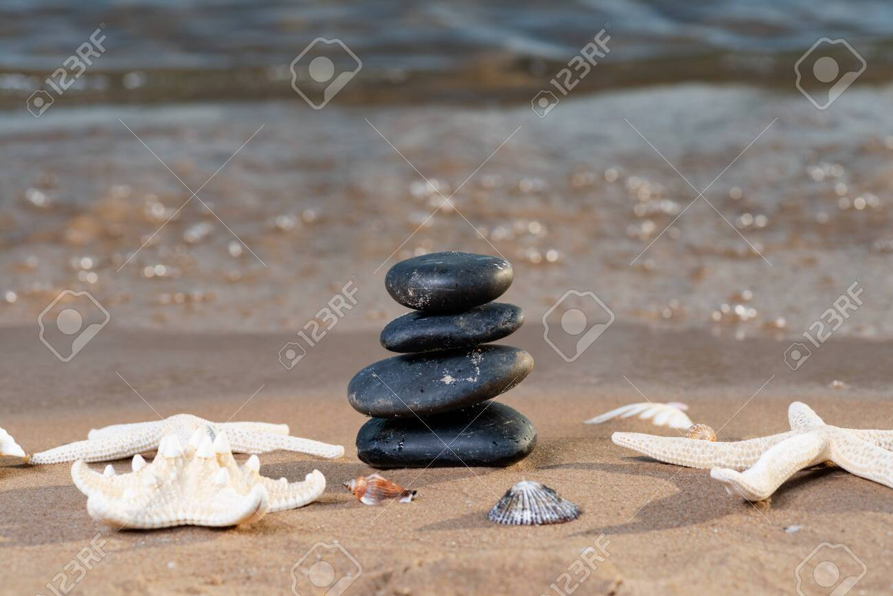 Spa composition - stacked Basalt Stones, Seashells and Sea Stars on the beach at sunrise in front of the ocean. Wellness, Balance and Relax concept. - 128873574
