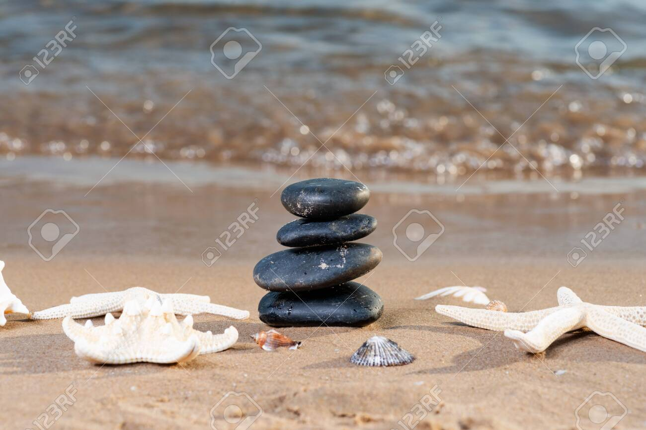 Spa composition - stacked Basalt Stones, Seashells and Sea Stars on the beach at sunrise in front of the ocean. Wellness, Balance and Relax concept. - 128873586