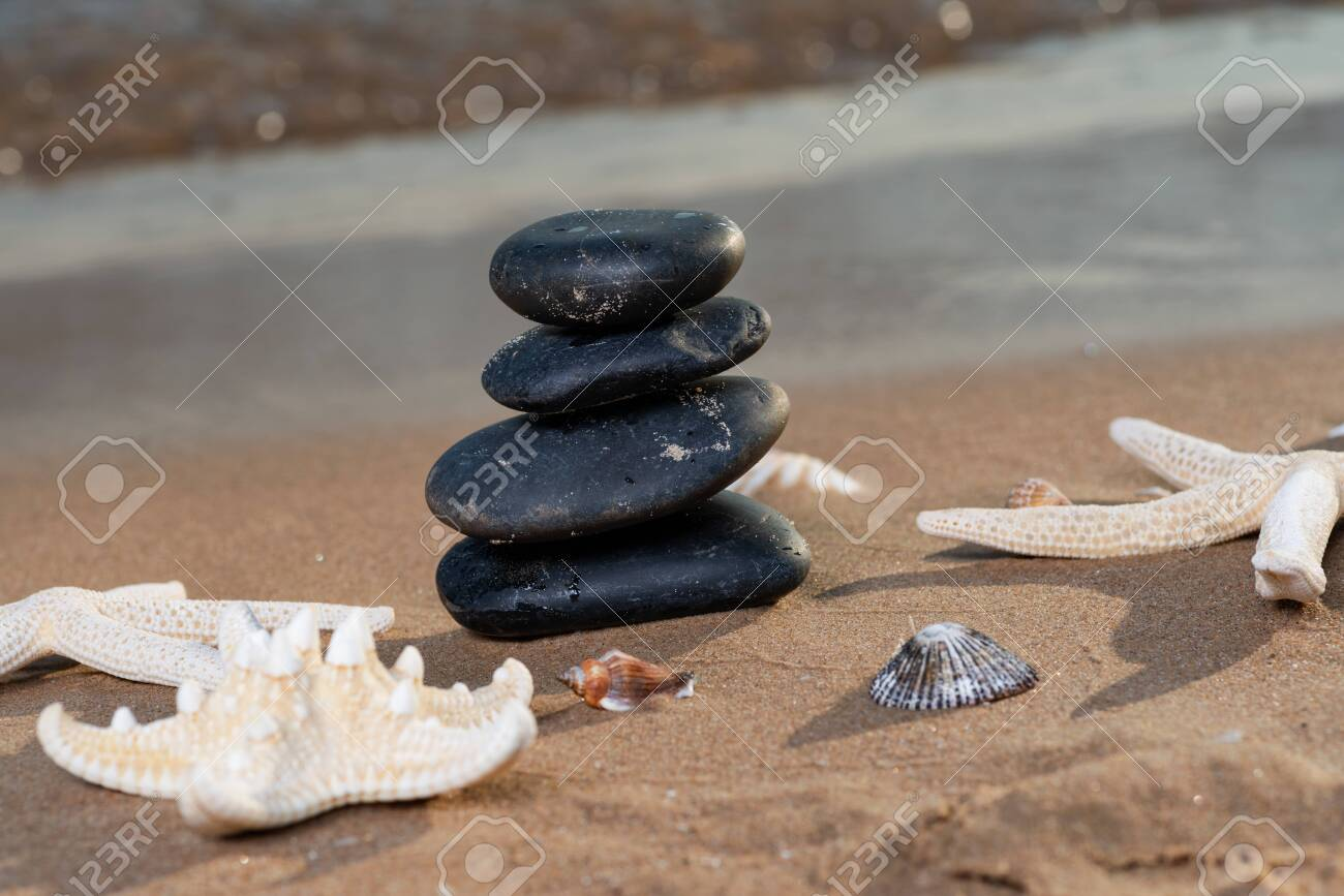 Spa composition - stacked Basalt Stones, Seashells and Sea Stars on the beach at sunrise in front of the ocean. Wellness, Balance and Relax concept. - 128873515