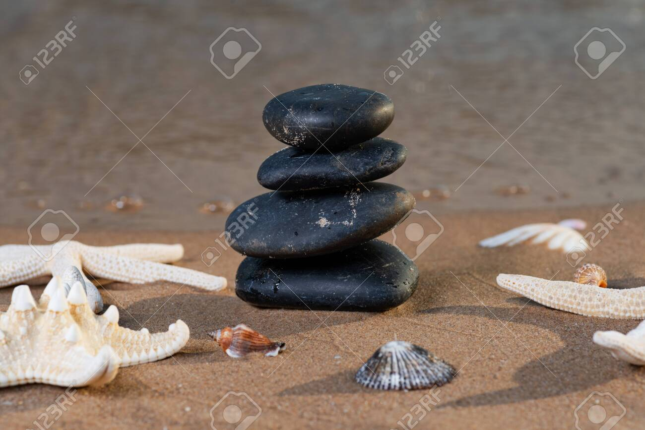 Spa composition - stacked Basalt Stones, Seashells and Sea Stars on the beach at sunrise in front of the ocean. Wellness, Balance and Relax concept. - 128873516