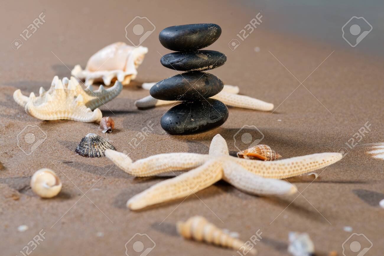 Spa composition - stacked Basalt Stones, Seashells and Sea Stars on the beach at sunrise in front of the ocean. Wellness, Balance and Relax concept. - 128873519