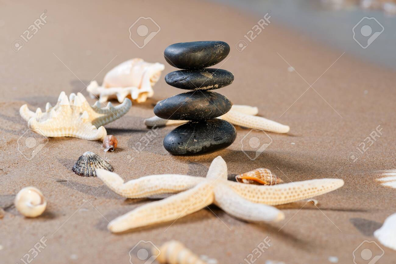 Spa composition - stacked Basalt Stones, Seashells and Sea Stars on the beach at sunrise in front of the ocean. Wellness, Balance and Relax concept. - 128873521