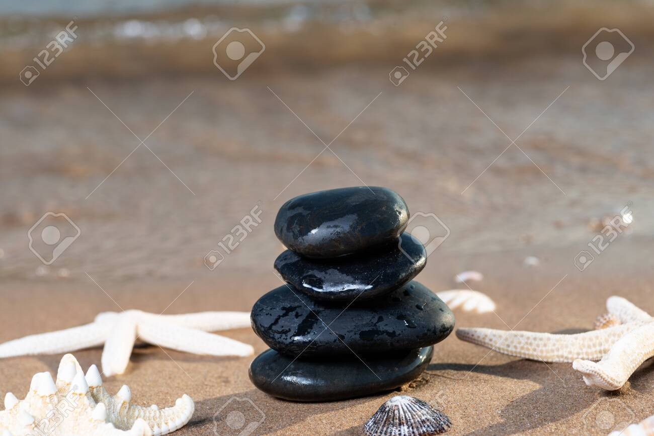 Spa composition - stacked Basalt Stones, Seashells and Sea Stars on the beach at sunrise in front of the ocean. Wellness, Balance and Relax concept. - 128873522