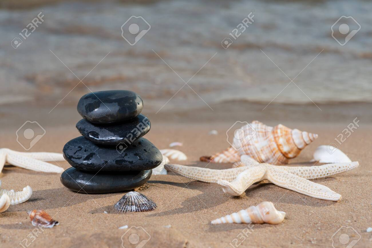Spa composition - stacked Basalt Stones, Seashells and Sea Stars on the beach at sunrise in front of the ocean. Wellness, Balance and Relax concept. - 128873524