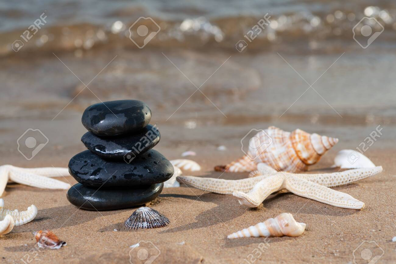Spa composition - stacked Basalt Stones, Seashells and Sea Stars on the beach at sunrise in front of the ocean. Wellness, Balance and Relax concept. - 128873526