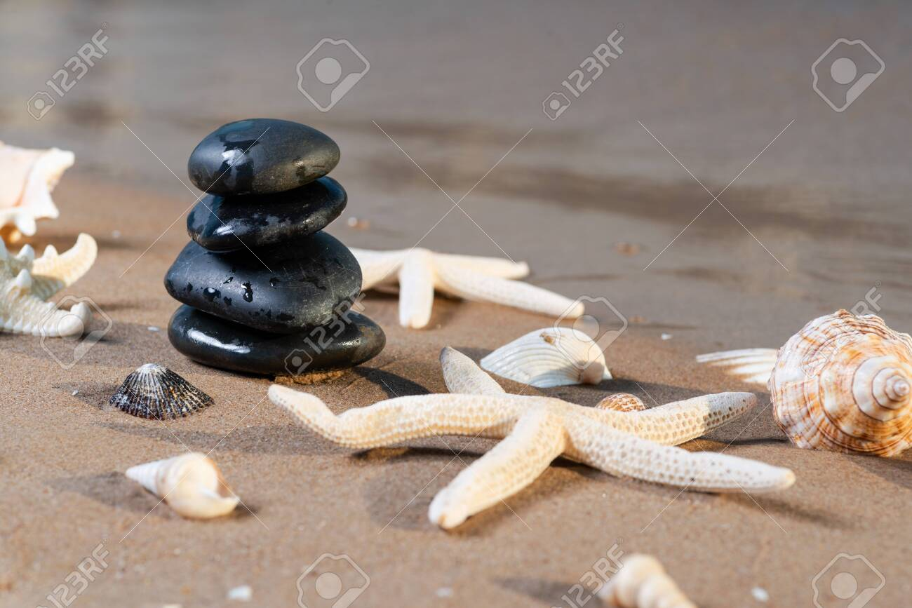Spa composition - stacked Basalt Stones, Seashells and Sea Stars on the beach at sunrise in front of the ocean. Wellness, Balance and Relax concept. - 128873525