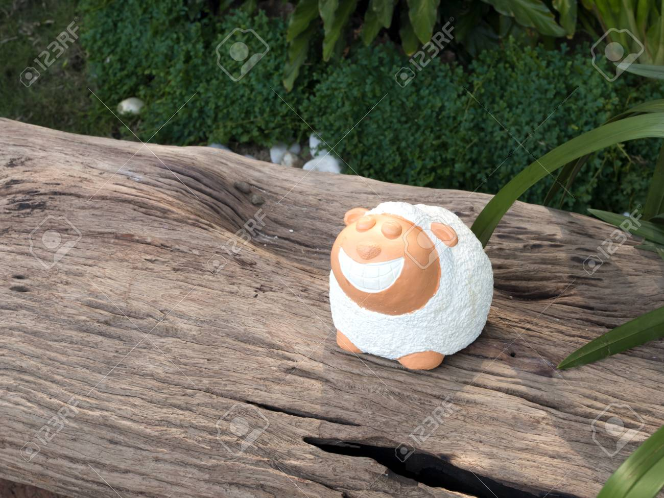 little sheep garden decorative statue on the log Stock Photo - 17902735