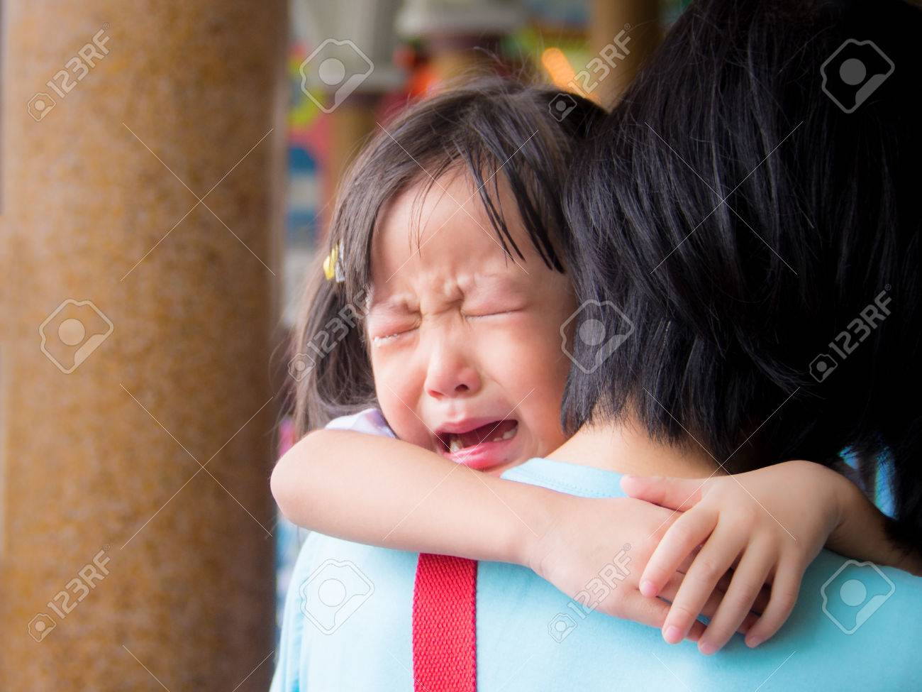 Asian baby girl hugging her mother crying - 58113867
