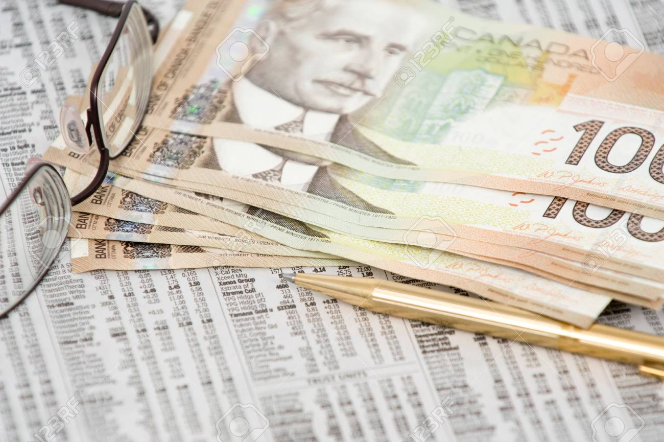 Canadian 100 Dollar Bill On Top Of Stock Market Quotes With Eye