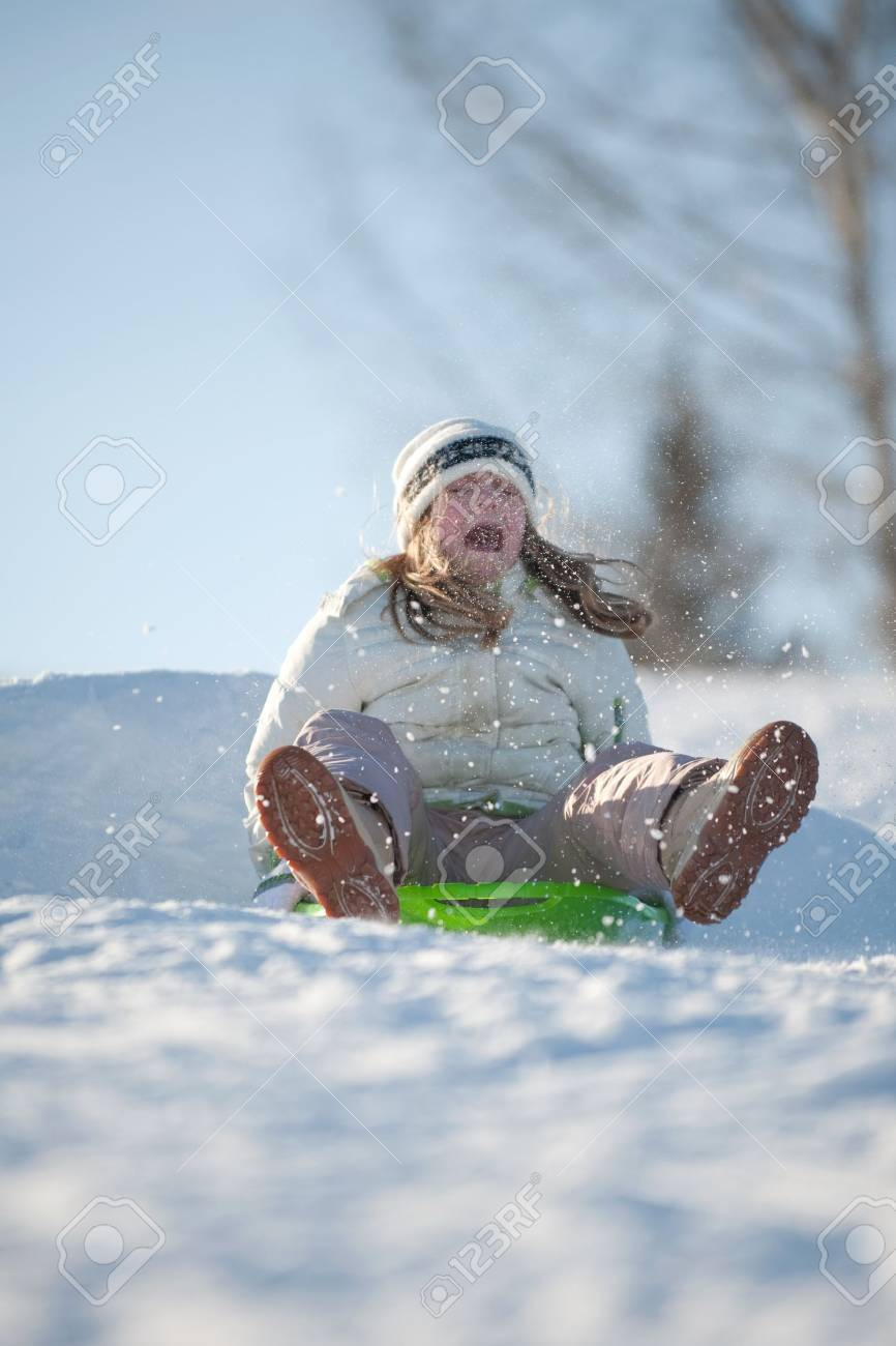 girl landing sled after going over a jump - 4398395