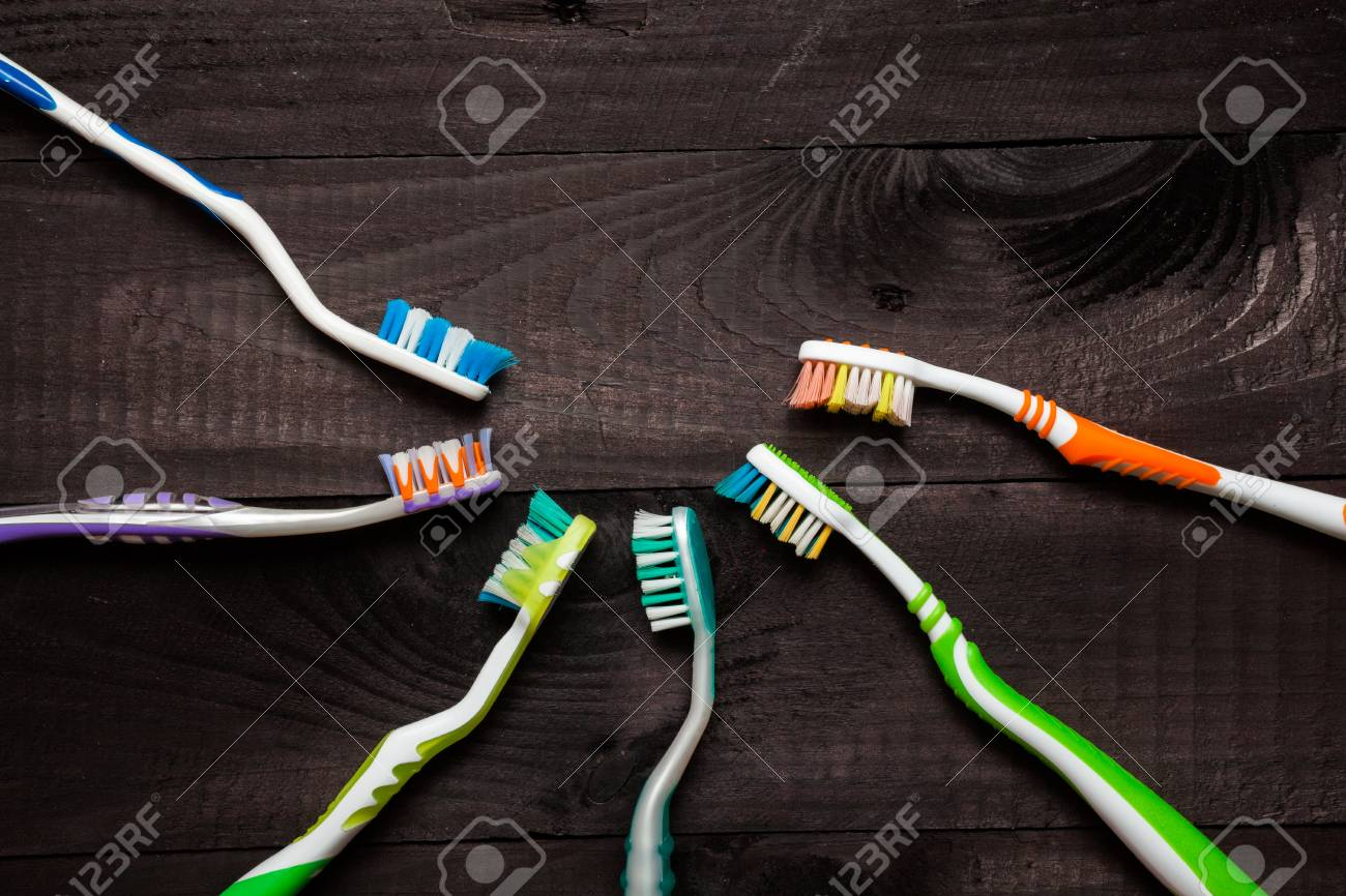 Colorful toothbrushes on black wooden background Stock Photo - 27056944