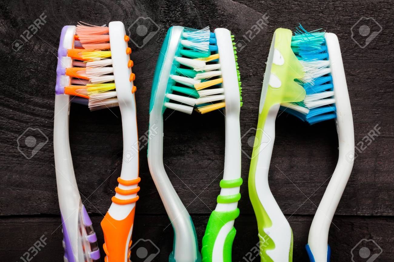 Colorful toothbrushes on black wooden background Stock Photo - 27056690