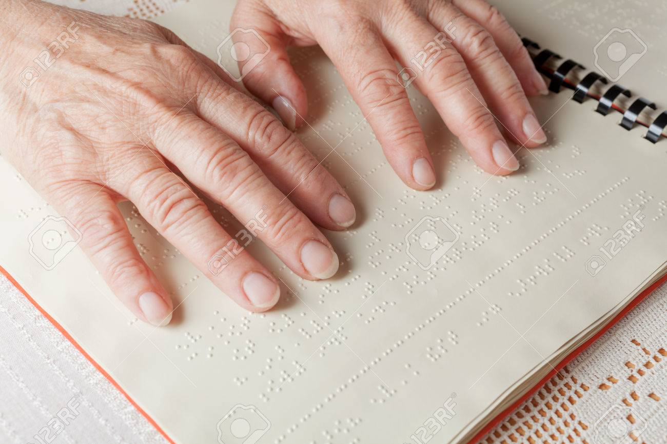 Blind old woman reading text in braille language Stock Photo - 27690198