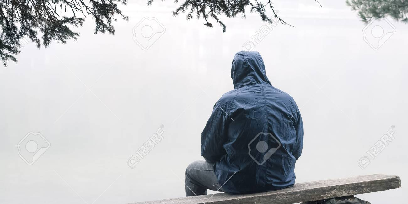 Depressed man sitting on bench in hooded jacket - 88649354