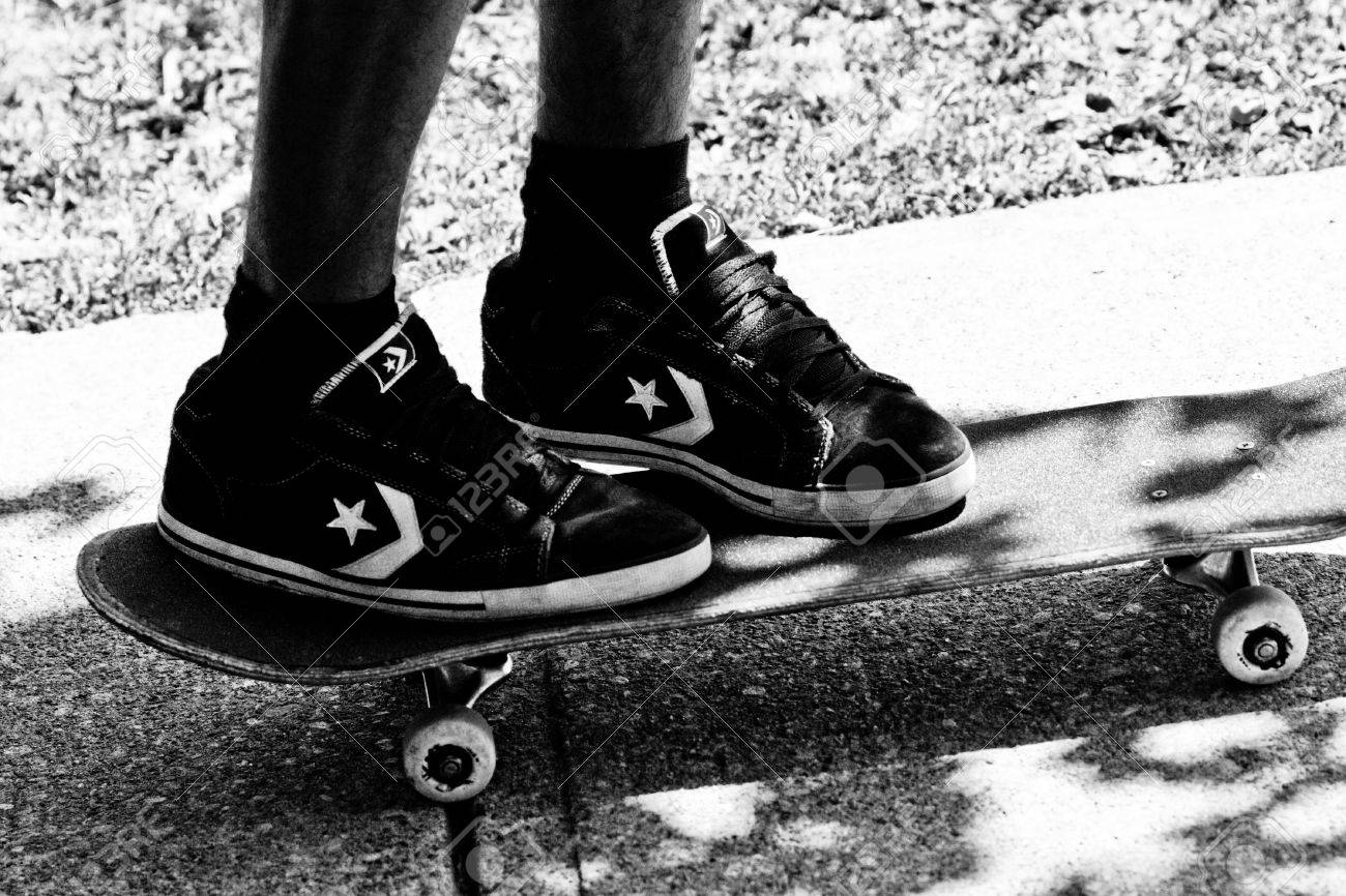 1164f2cb6b2 Teen Wearing Converse Skate Shoes Stands On A Skateboard Stock Photo ...