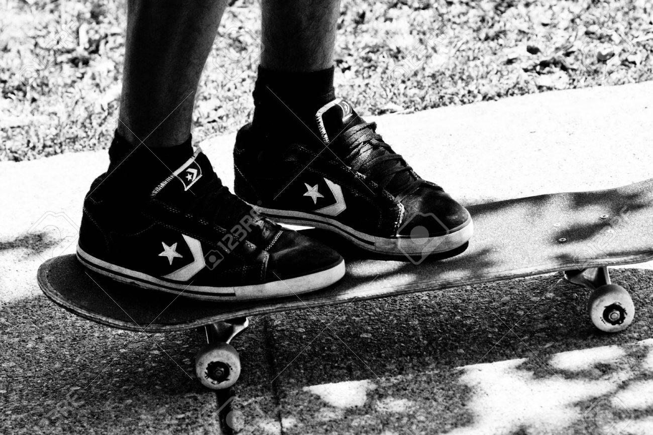 nieuwe specials hete verkoop online om te kopen Tiener draagt ??Converse skate schoenen staat op een skateboard