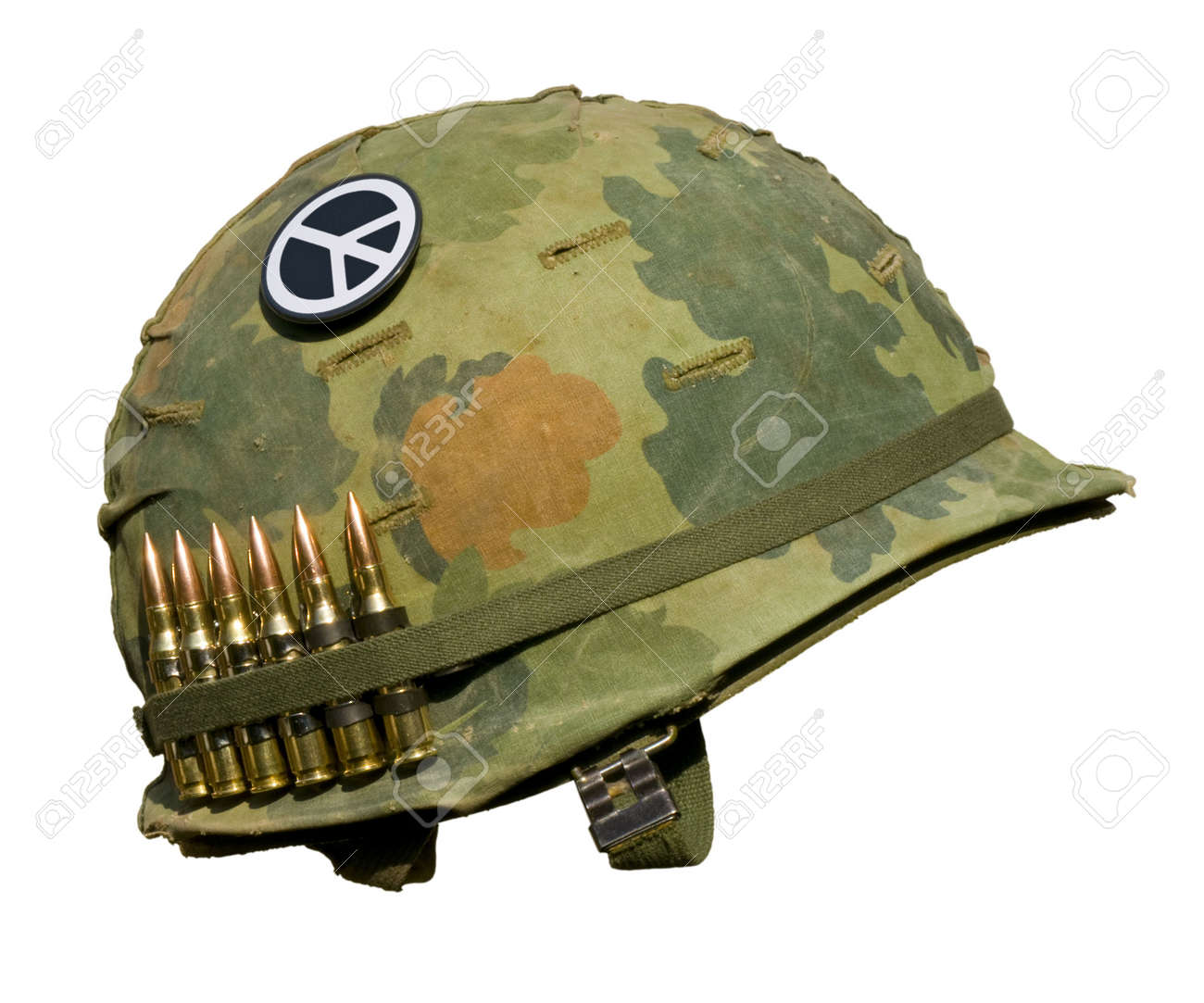 A US military helmet with an M1 Mitchell pattern camouflage cover from the Vietnam war, with six rounds of 7.62mm ammunition and a peace symbol button. Stock Photo - 5783284