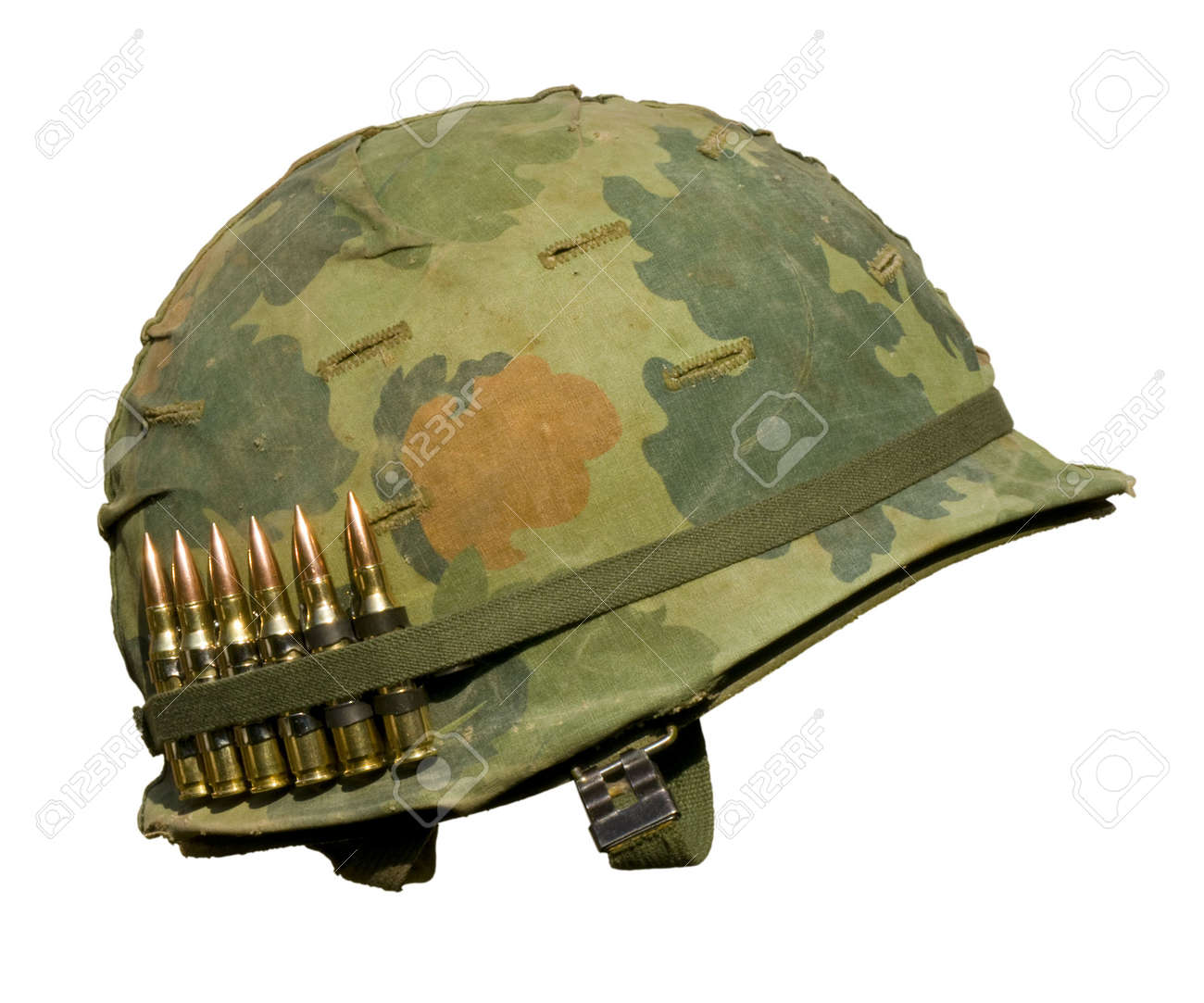 A US military helmet with an M1 Mitchell pattern camouflage cover from the Vietnam war, and six rounds of 7.62mm ammunition. Stock Photo - 5783283