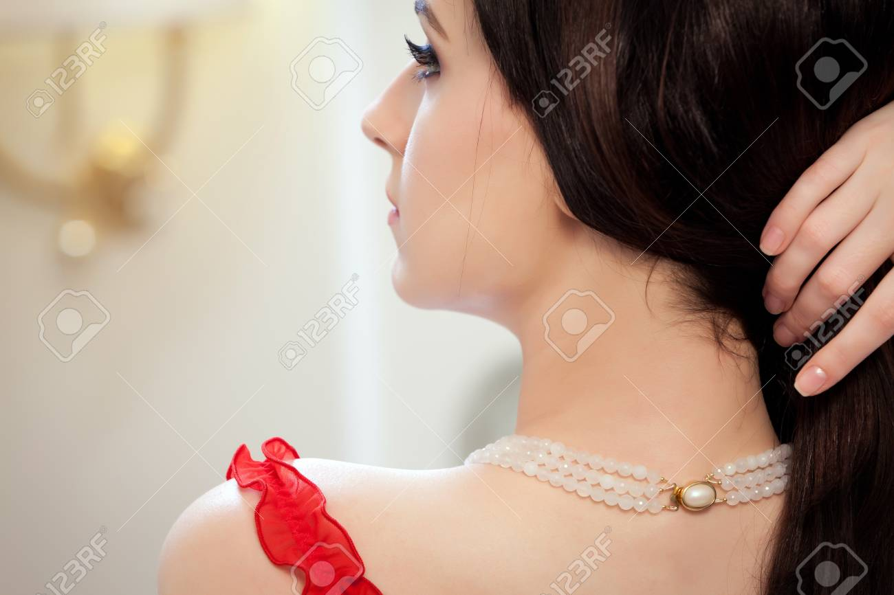 Lovely brunette in a vintage style bedroom  Focus on the necklace trap Stock Photo - 13653550