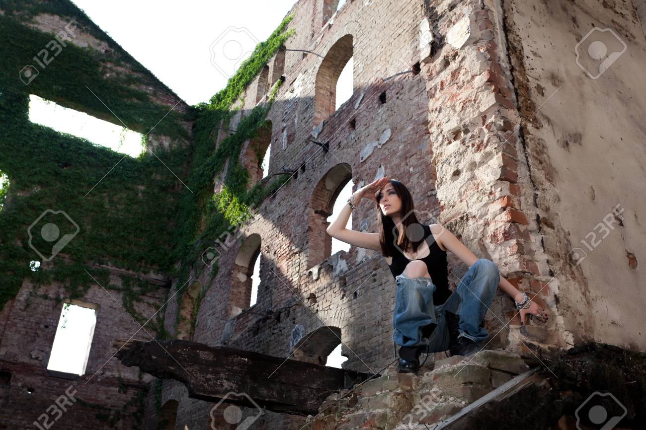 Woman in jeans in a deserted building looking to see if there is somebody coming Stock Photo - 20680856