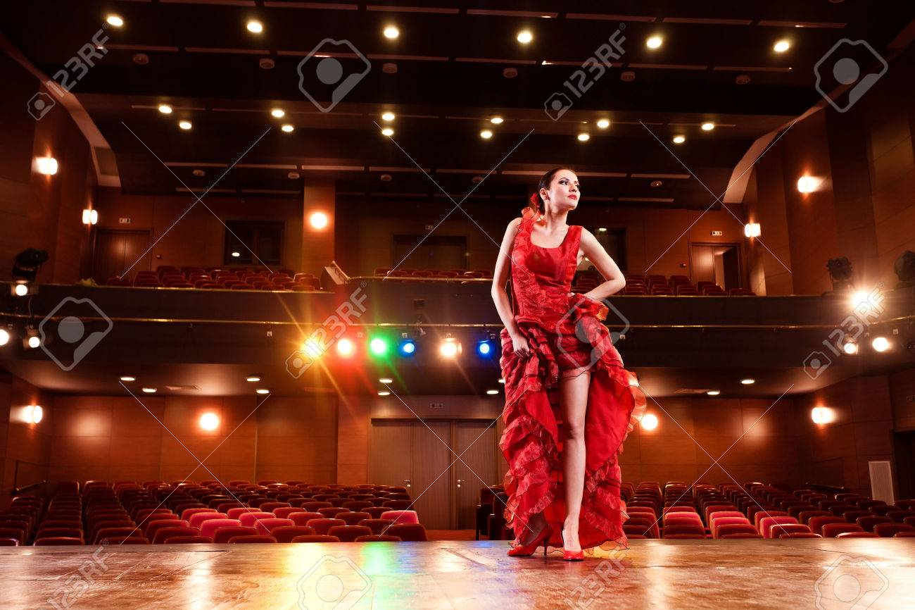 flamenco dancer performing her dance in a red long dress