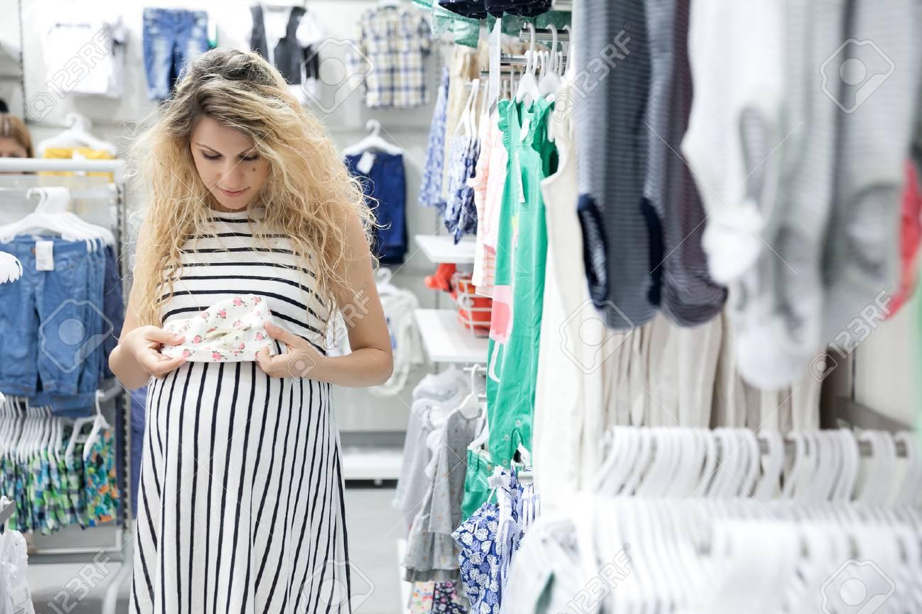 ce75c0bcd Foto de archivo - Mujer embarazada encantadora joven en busca de un poco de  ropa de bebé en una tienda para su nuevo bebé.