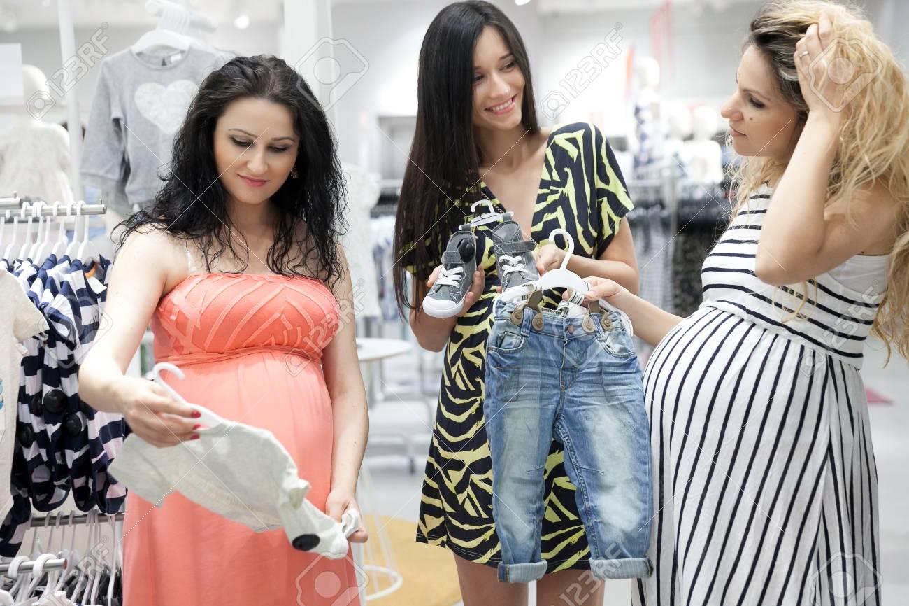 d72ec8535 Foto de archivo - Las mujeres embarazadas jóvenes encantadores que buscan  un poco de ropa de bebé en una tienda para sus nuevos bebés.