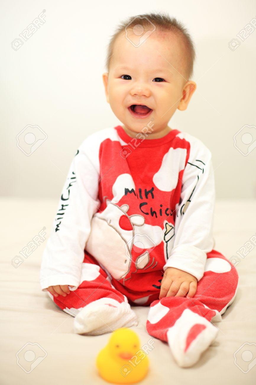 7128b5ab4533c Banque d images - Rire bébé asiatique mignon avec rouge vache pyjama sur le  lit. Studio shot avec garçon de 6 mois