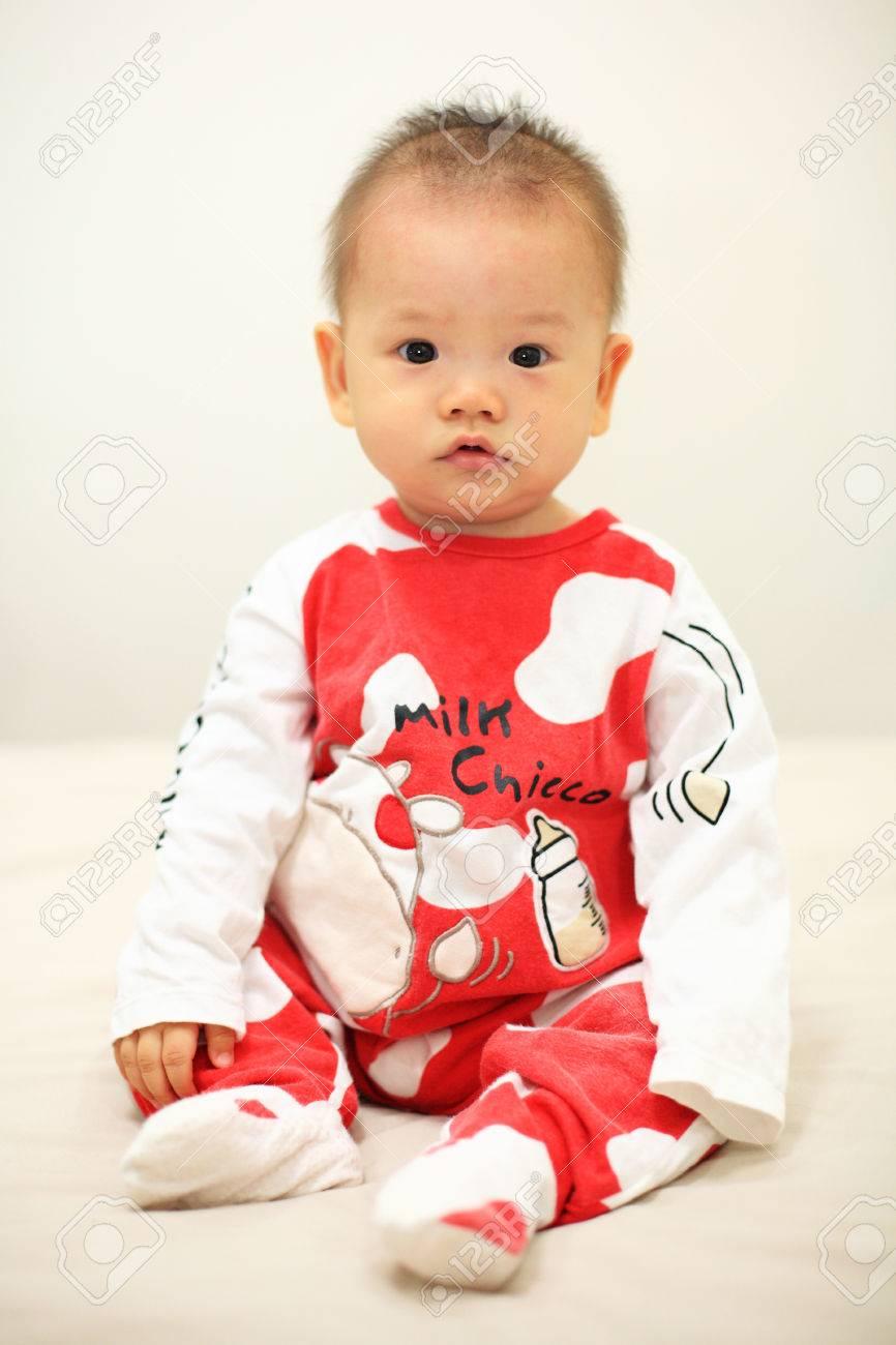 1b4cf0e2e66a0 Banque d images - Curieux bébé asiatique mignon avec rouge vache pyjama sur  le lit. Studio shot avec garçon de 6 mois