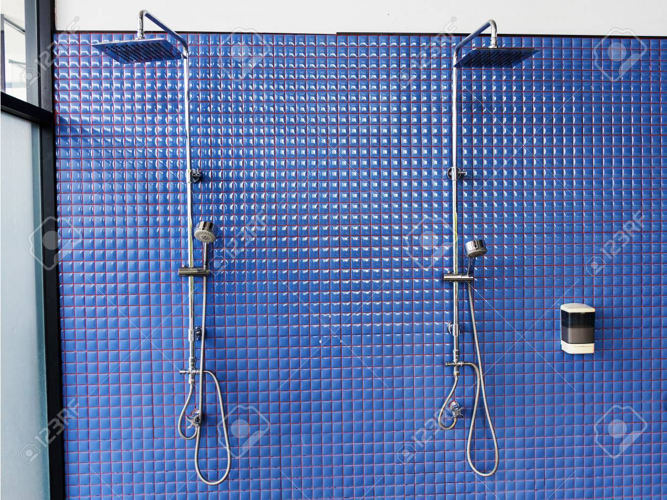 Public shower on blue tile wall of swimming pool