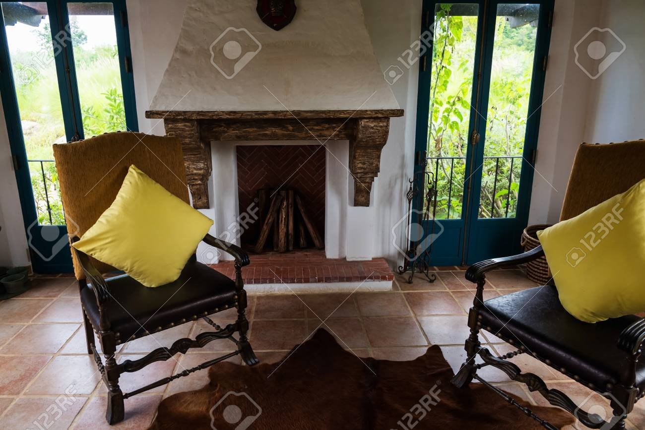 Interior Of Old Country House With Antique Chairs And Fireplace Stock Photo