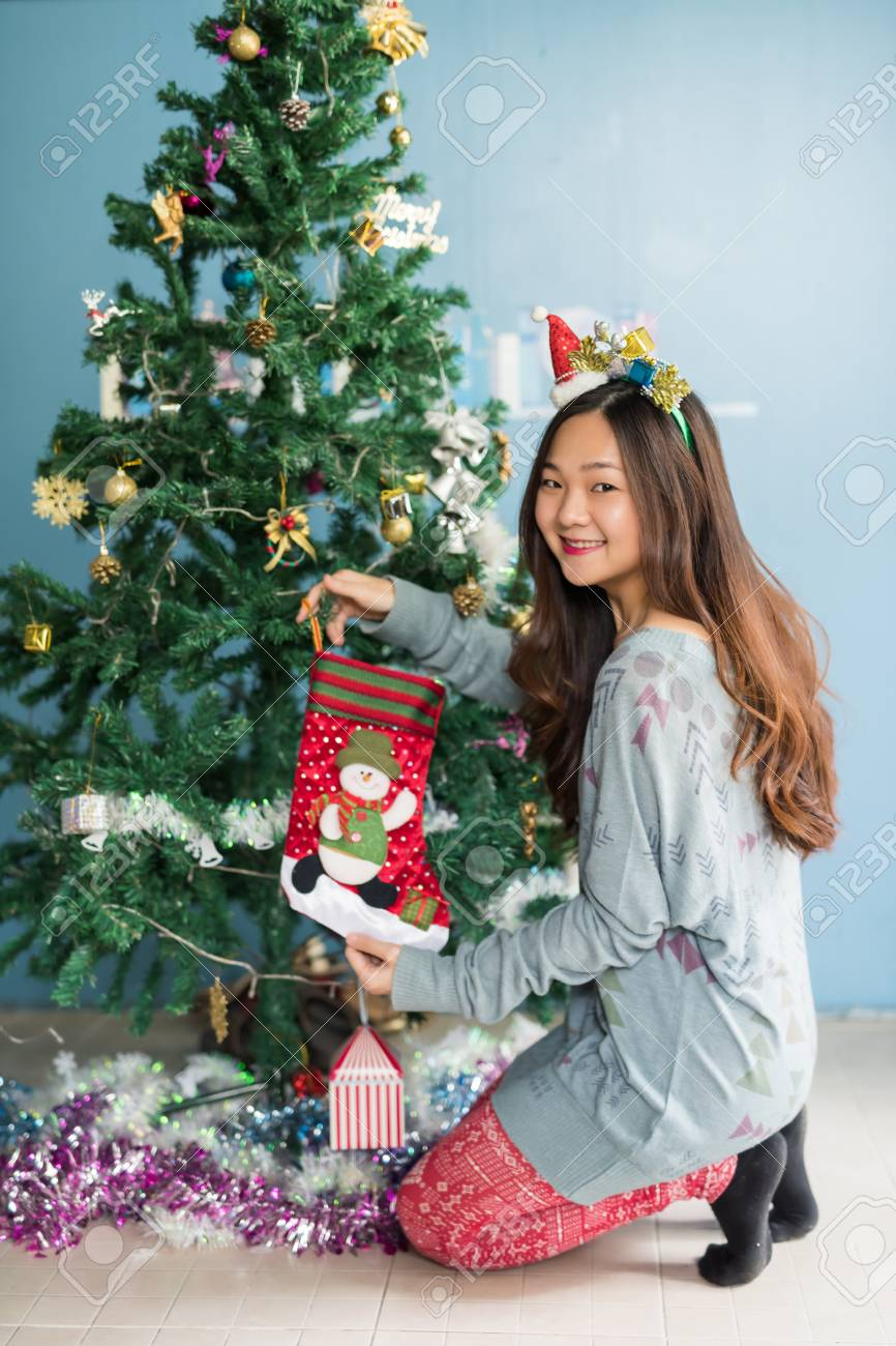 Asian Christmas Girl Hides Gifts In Socks To Attach On Xmas Tree