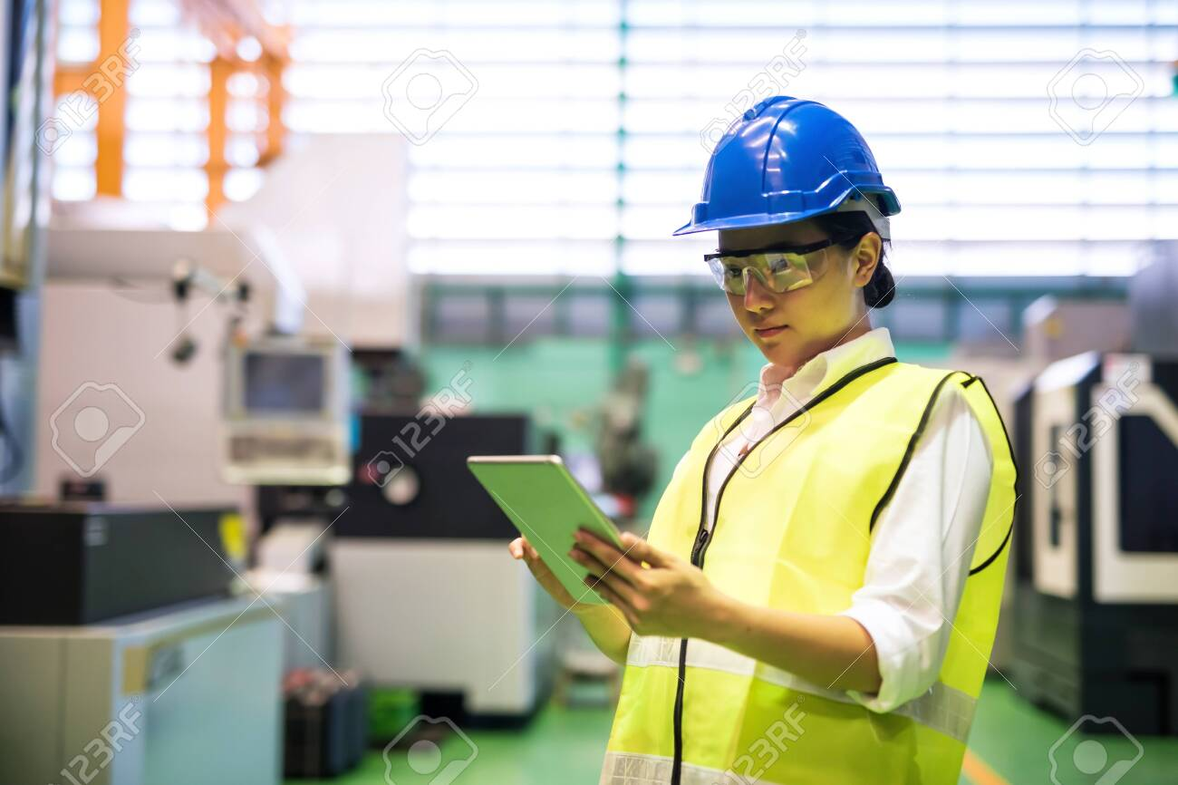Waist up female worker with hardhat and protection glasses use corporate applciation to check automate robot machines in factory. Manufacture industry with technology. social distancing during covid-19. - 146216929