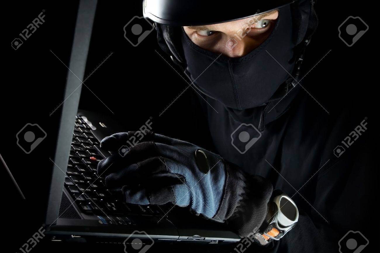 Security concept with sneaky thief and laptop at night Stock Photo - 6676718