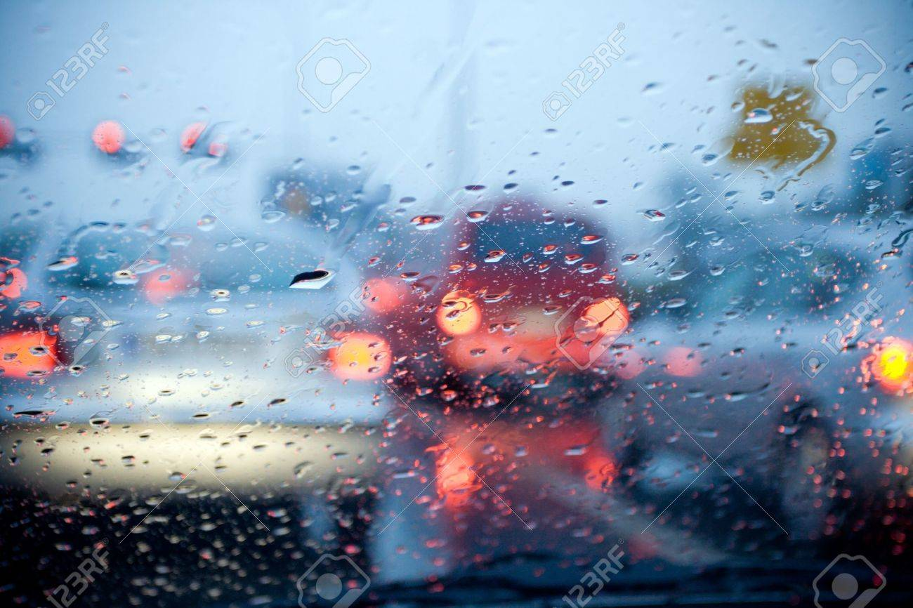 Car windshield with rain drops during storm and blurred stoplights.