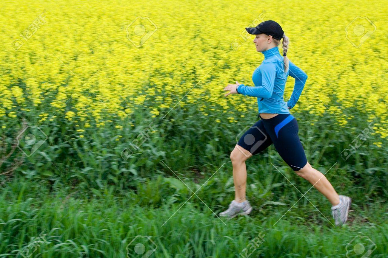 Athlete female runner training outdoors over yellow colza, motion blur. Stock Photo - 7037459