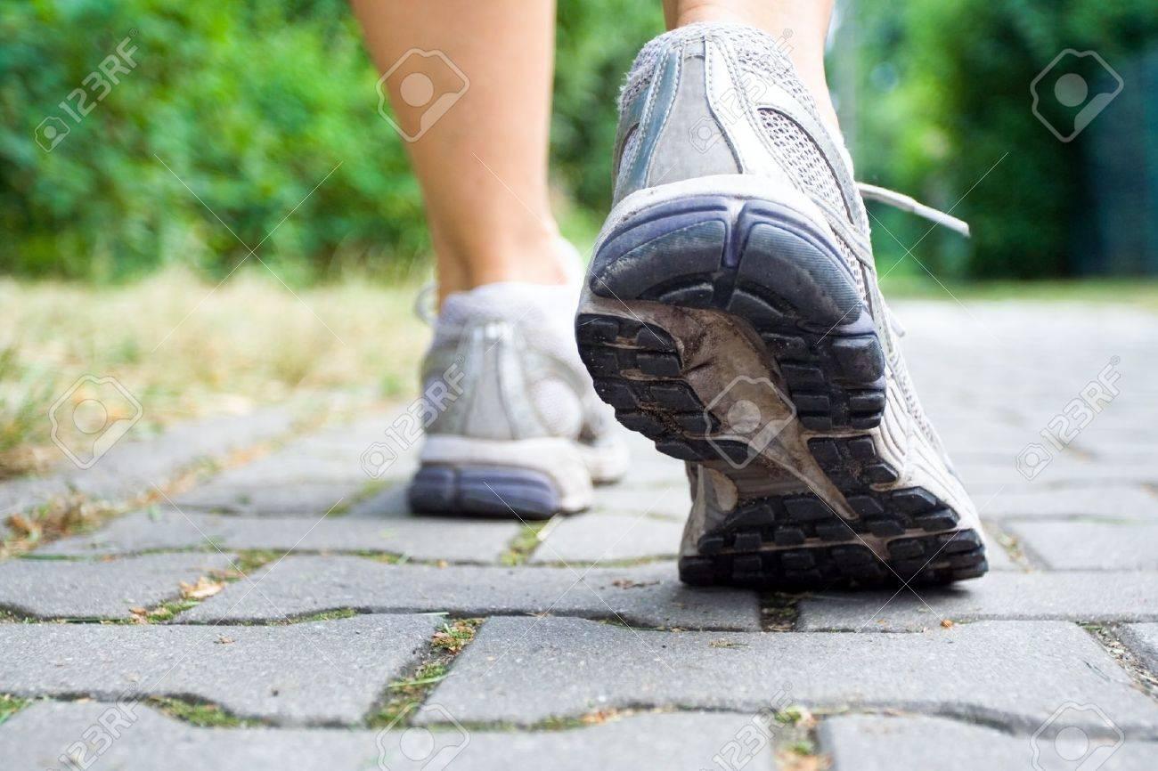 Woman walking on sidewalk, sport shoes close-up Stock Photo - 7712259