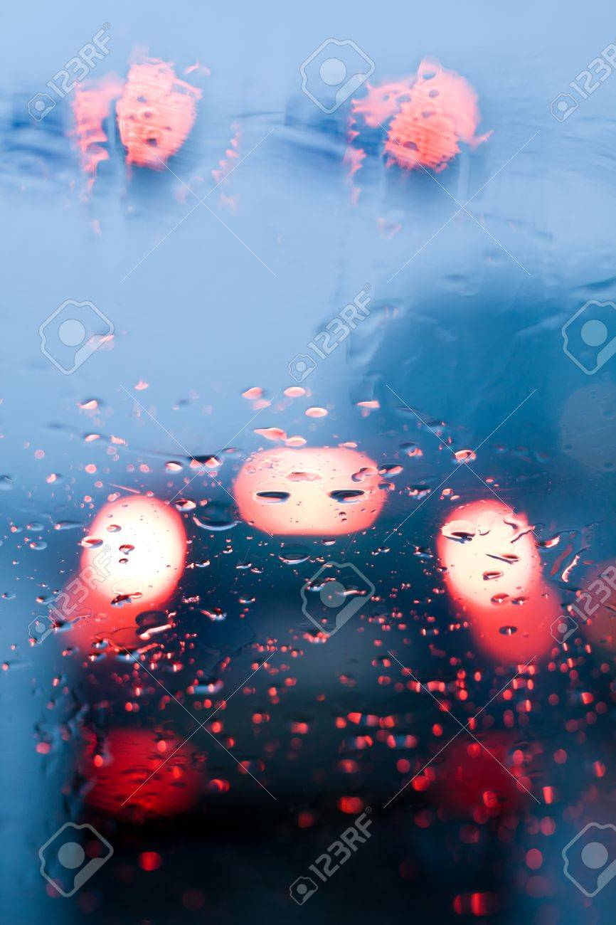 Traffic jam from inside a car during storm with rain drops on window.Shallow depth of field with focus on center of the windshield with red lights. Stock Photo - 9305972