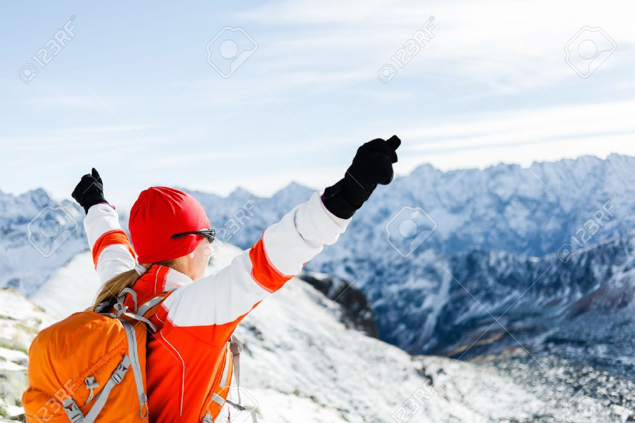 Hiking woman and success in winter mountains. Fitness and healthy lifestyle outdoors in snowy nature. Female mountaineer or climber on top of mountain peak happy with arms raised. - 16715154