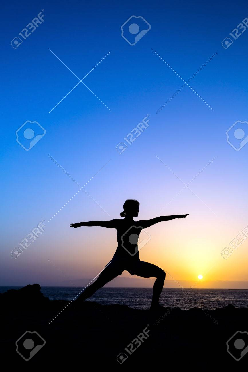 Young Woman Doing Yoga Pose Warrior One Sunset Silhouette In