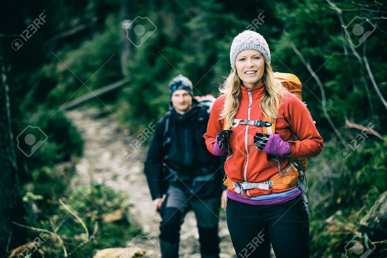 Man and woman happy couple hikers trekking in green autumn forest and mountains. Young people walking on trail with backpacks, healthy lifestyle adventure, camping on hiking trip, old vintage photo style. - 41350481