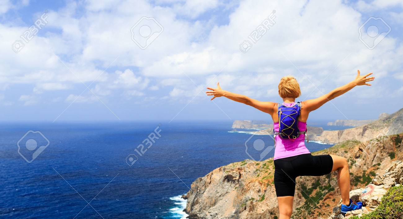 Success achievement running, climbing or hiking accomplishment concept, woman celebrating with arms up raised outstretched hiking, climbing or trail running healthy lifestyle - 42152567