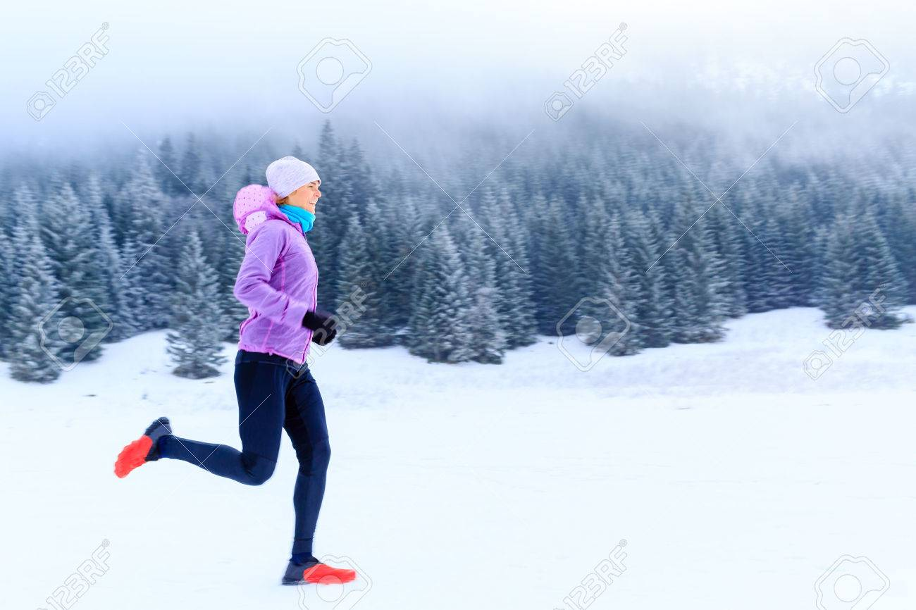 Sport, fitness inspiration and motivation. Young happy woman cross country running in mountains on snow, winter day. Female trail runner jogging exercising outdoors. - 43899652